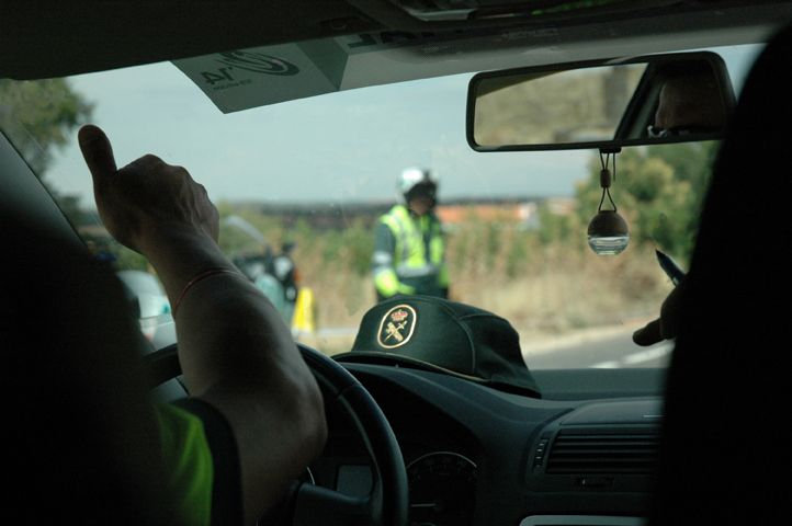 Un guardia civil se comunica desde elcoche con su compañero.